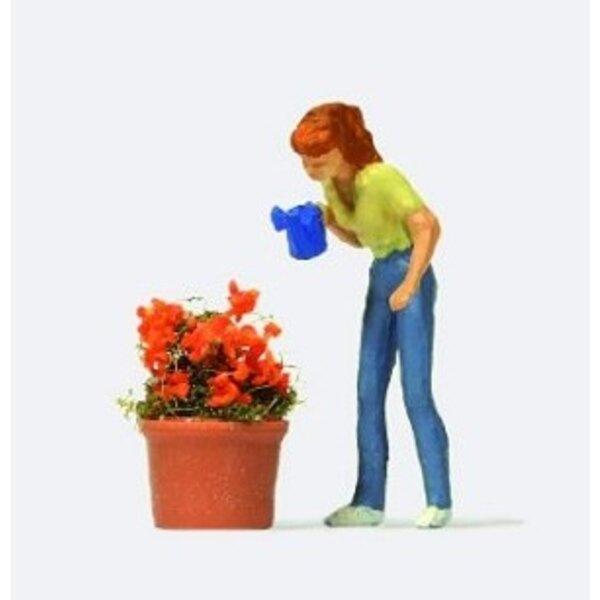 Donna innaffiamento di un vaso di fiori